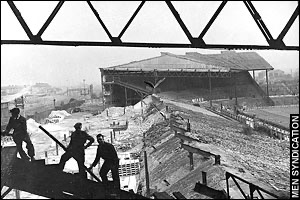 Image show a black and white photograph of Old Trafford football stadium, which is laying in rubble following a bombing.