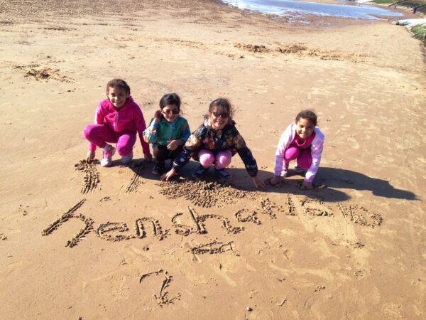 4 children writing Henshaws in the sand on a beach