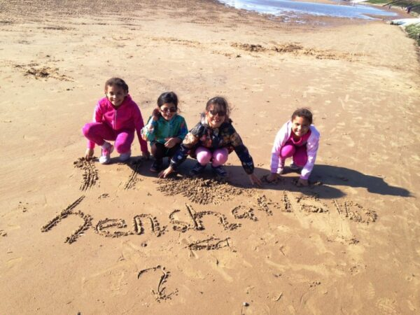 4 young children writing Henshaws in the sand on a beach
