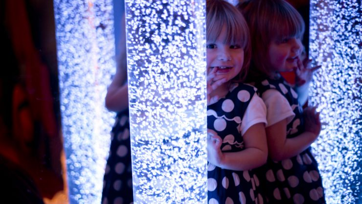 Photo of a child hiding behind a crystal structure