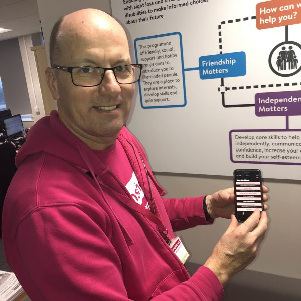 Image shows a member of Henshaws staff wearing a pink t-shirt and hoodie. He is holding a mobile phone, showing the Talking Newspaper app on the screen.
