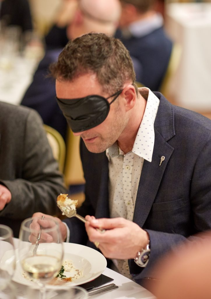 A man in a blindfold lifting a fork to his mouth