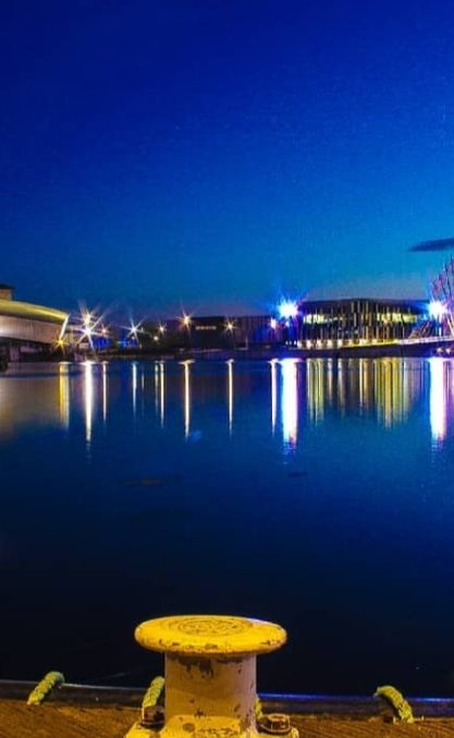 A sky line at Salford Quays with the water in the foreground and the Imperial War Museum North in the background