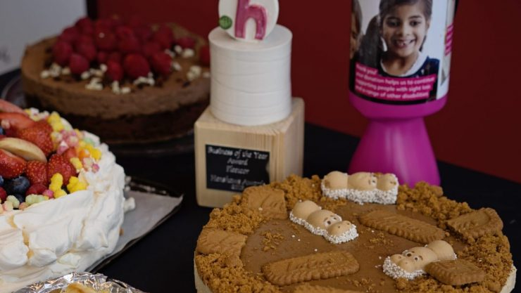 A selection of cakes on a table next to a Henshaws award and pink collection tin