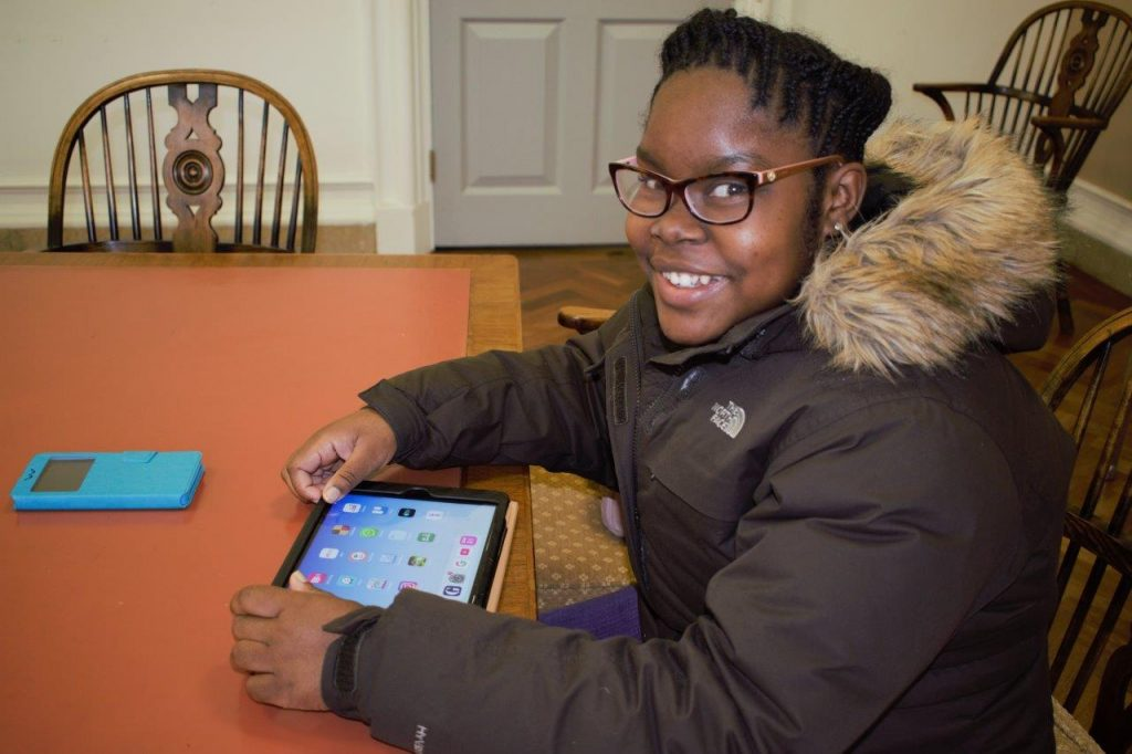 Image shows young woman sat at a desk holding a tablet device and smiling at the camera.