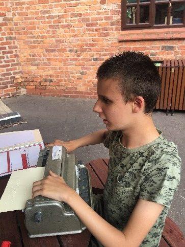Child sat at a braille machine.