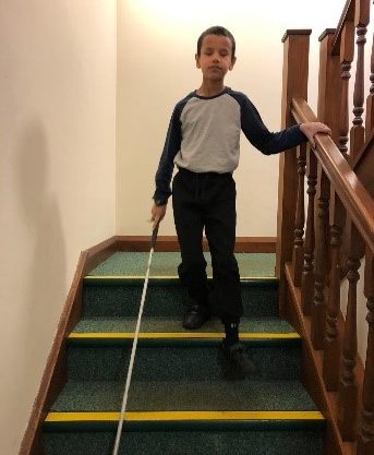 Boy walking down stairs with a white cane.