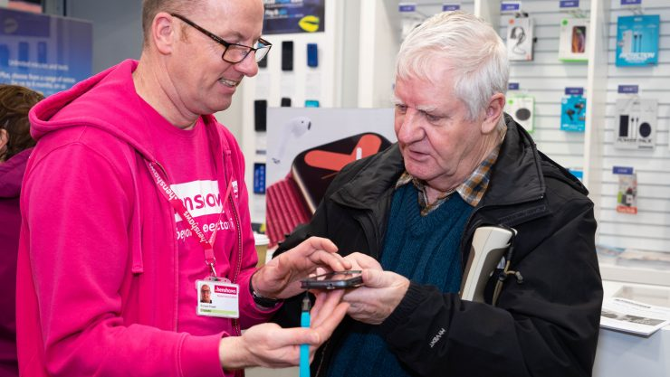 Image shows a member of Henshaws staff demonstrating a smartphone to a visually impaired man.