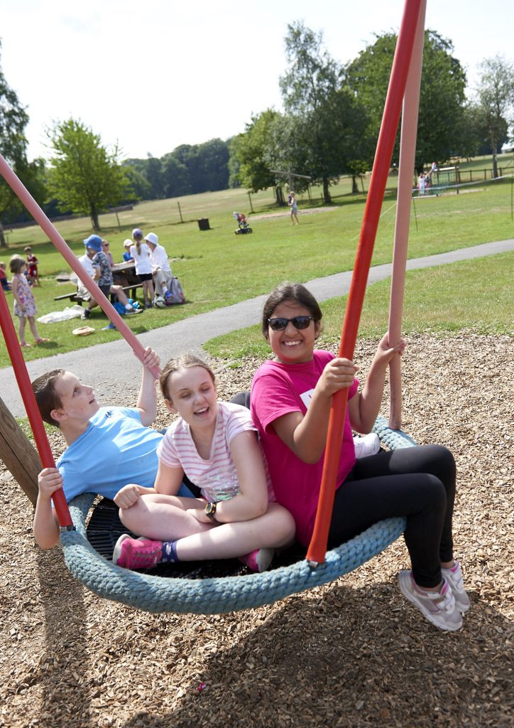 Image shows three children sat on a large swing and smiling.