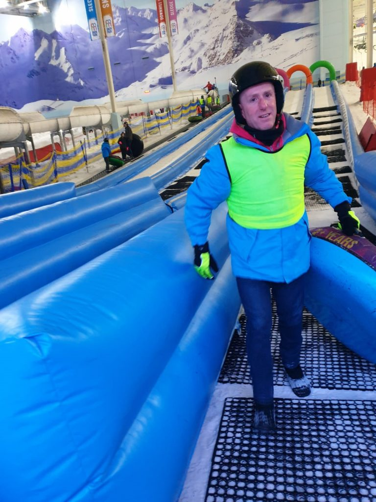 Image shows George wearing a high-vis vest whilst taking part in activities at the indoor snow park.