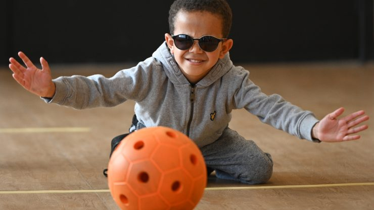 Image shows a young boy wearing dark glasses, kneeling on the floor as a ball rolls towards him.