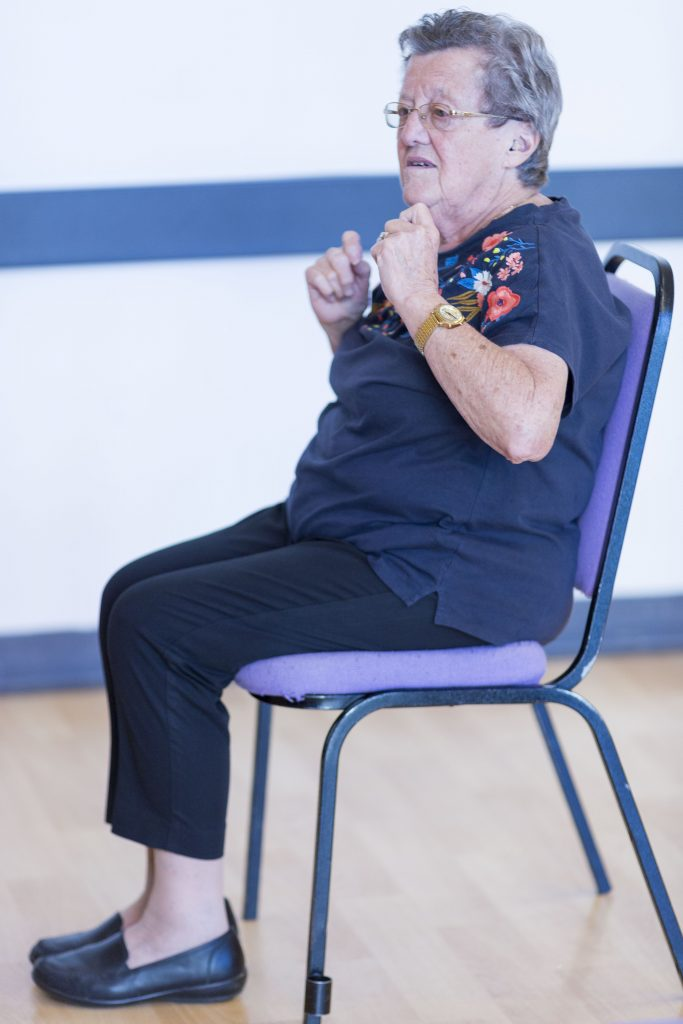 Image shows a lady sat on a chair, ready to stretch her arms
