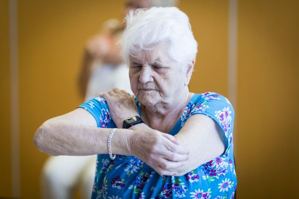 Image shows an elderly lady stretching her arms.