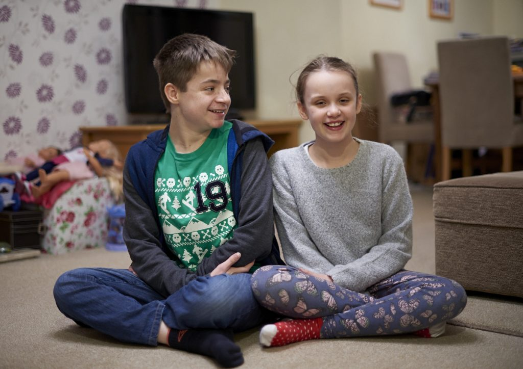 Image shows a boy and a girl sat cross-legged on the living room floor, both are smiling.