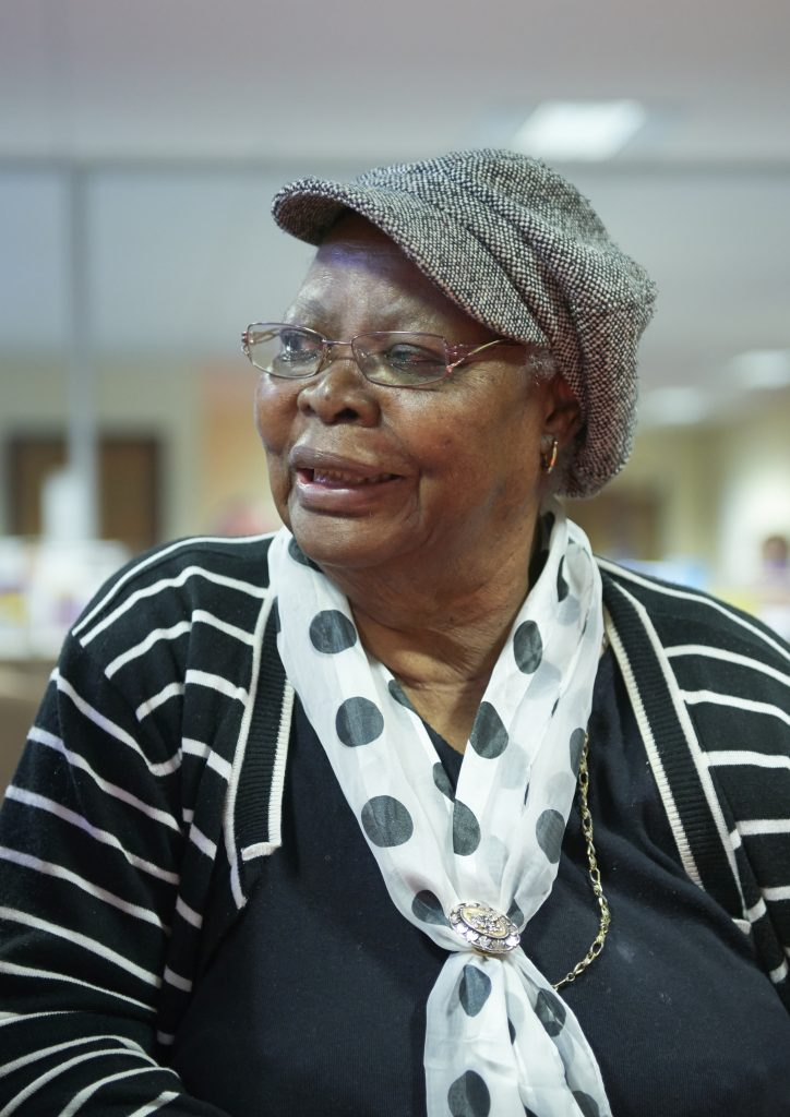 Image shows an elderly lady wearing glasses and smiling. She is wearing a spotty scarf.