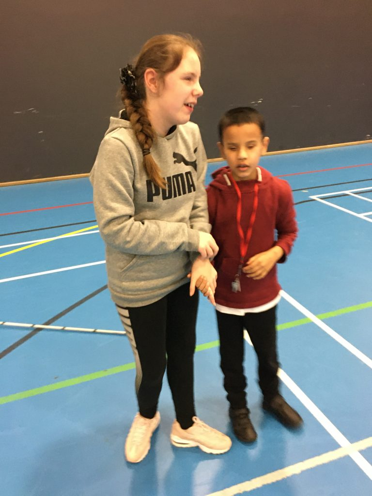 Image shows a young girl with a young boy, stood in a gym.