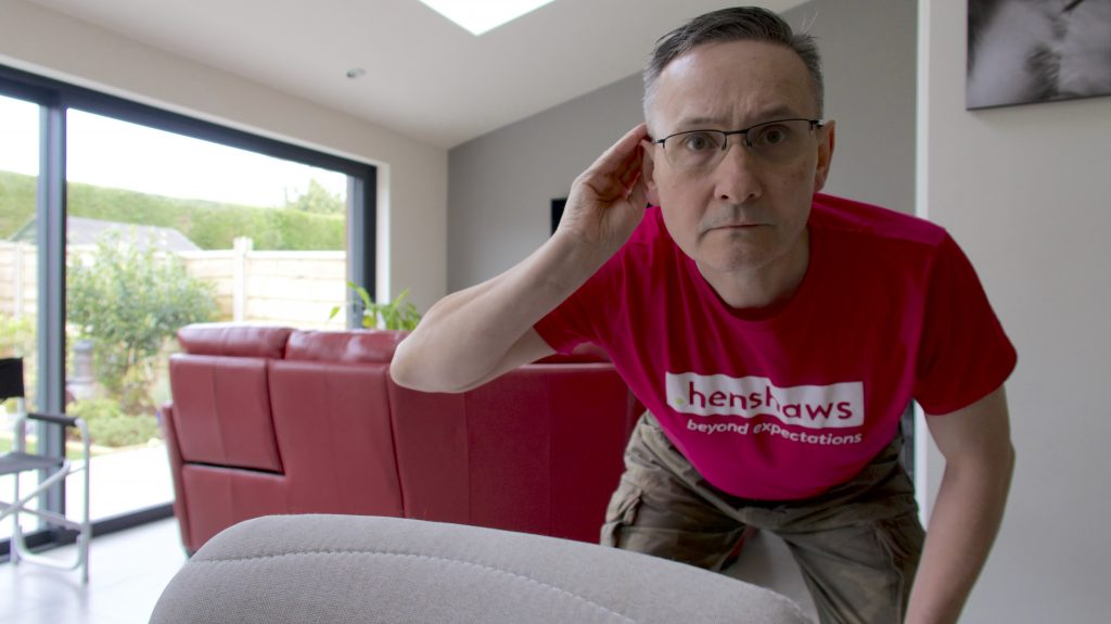Image shows a man wearing a pink Henshaws t-shirt. He is cupping his hand to his ear.