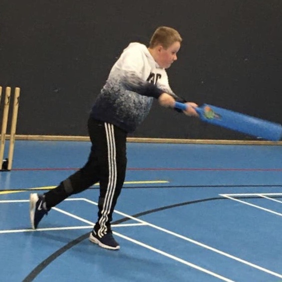 Image shows a boy holding a blue cricket bat, he has just hit the ball and is starting to run.