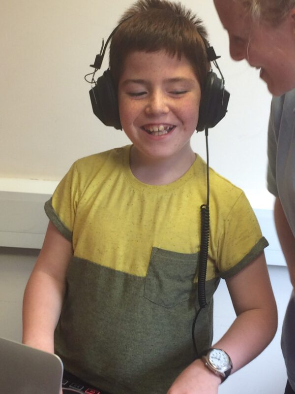 Image shows a young boy wearing headphones and listening to music.