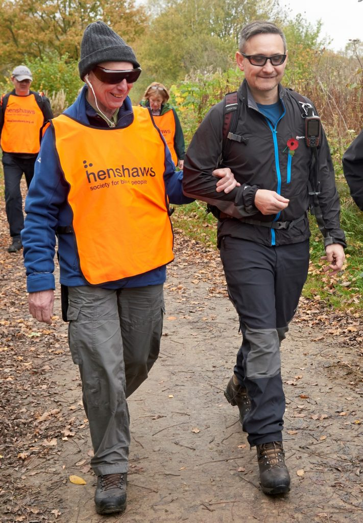 Image shows a man wearing a high visibility vest and dark glasses, being guided by another man.