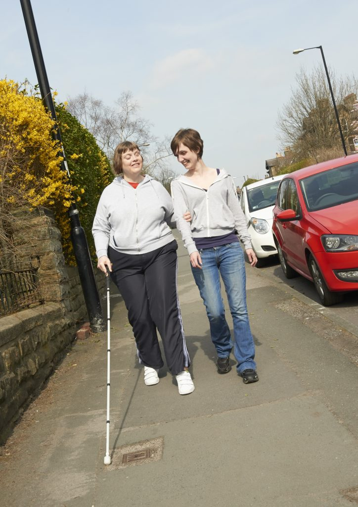 Image shows two woemn walking side by side; one woman is holding a long cane.