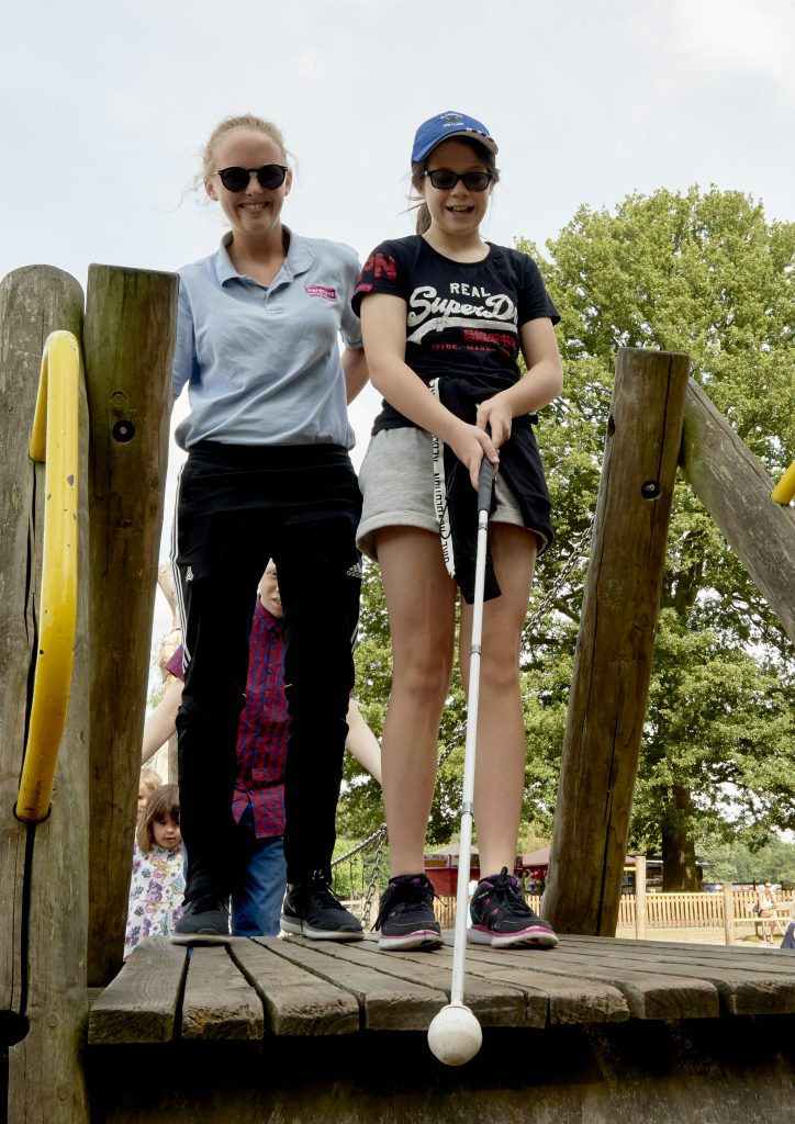 Image shows a girl using a long cane, with a meber of Henshaws staff next to her.