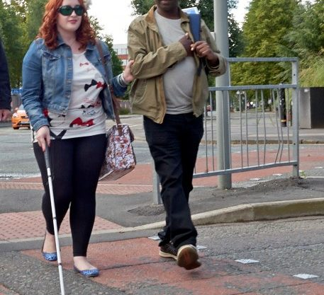 Image shows a woman holding a long cane and holding the arm of a man whilst crossing the road.