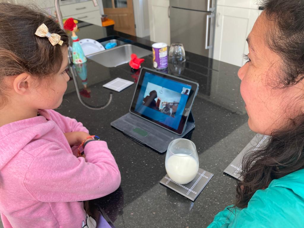 Image shows a young girl and a woman sat at a kitchen counter looking at a tablet device with two elderly people on the screen.