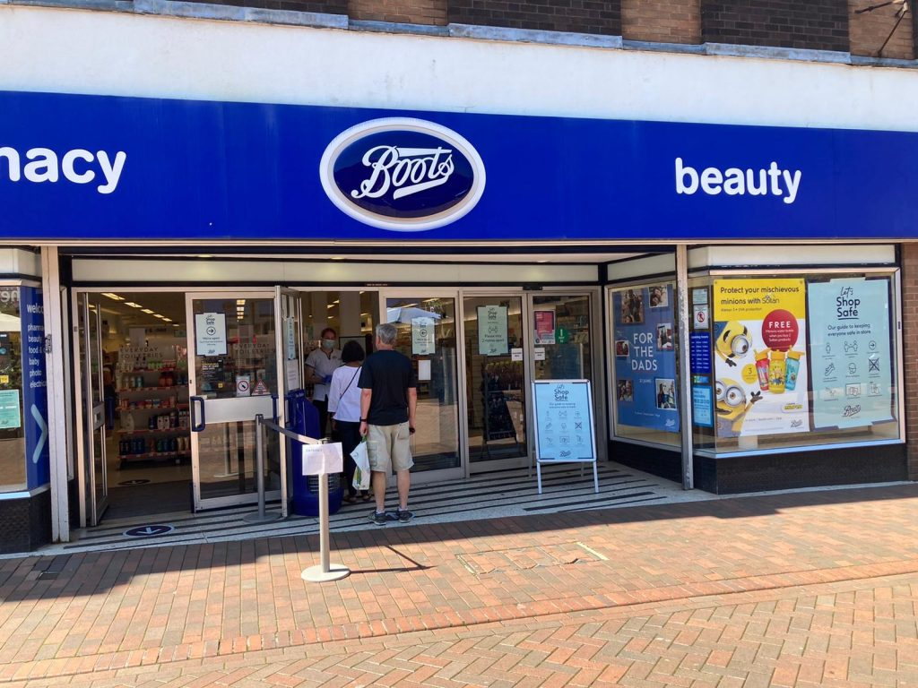 Image shows a Boots pharmacy with a social distancing queue out the front door.
