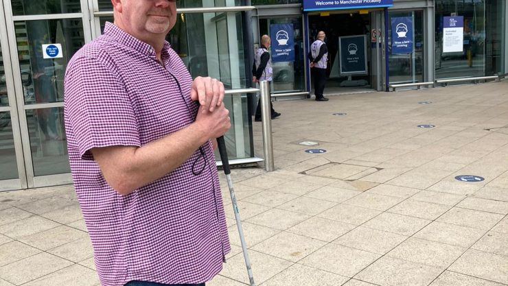 Simon holding long cane at Piccadilly station