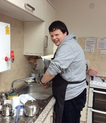 Student washing up in the kitchen
