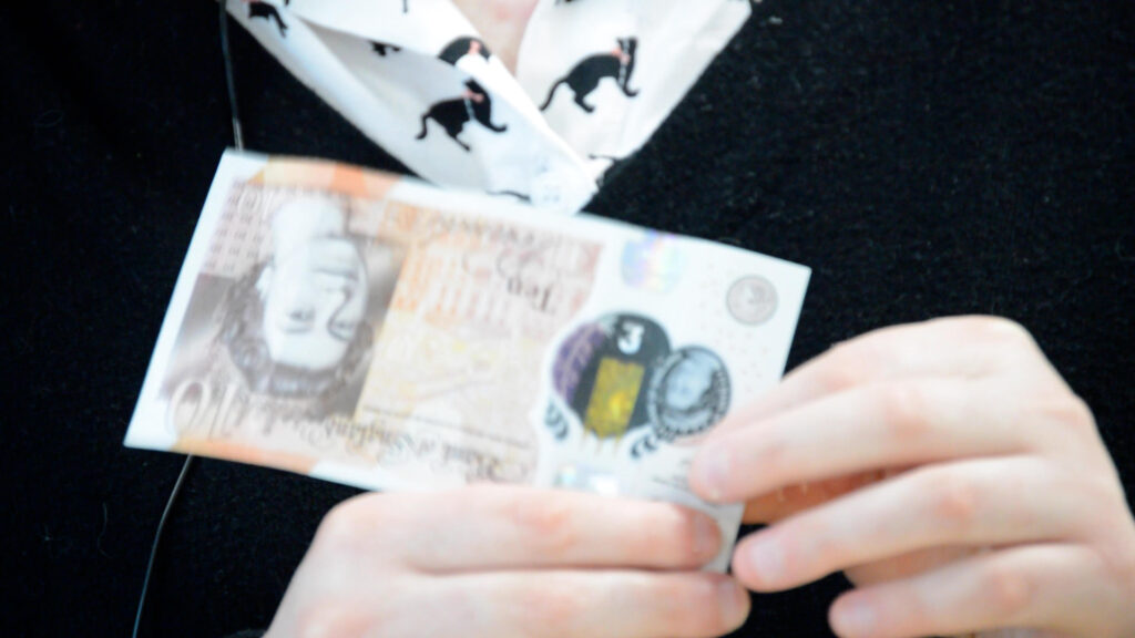Alice identifying a £10 note using the tactile feature