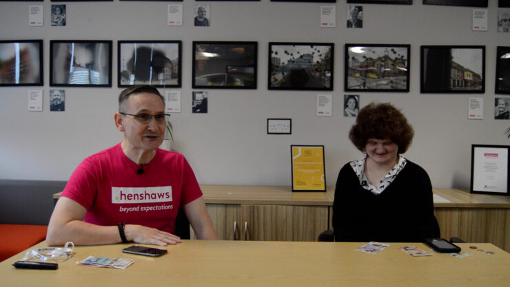 Mark and Alice facing the camera, with money visible on the table
