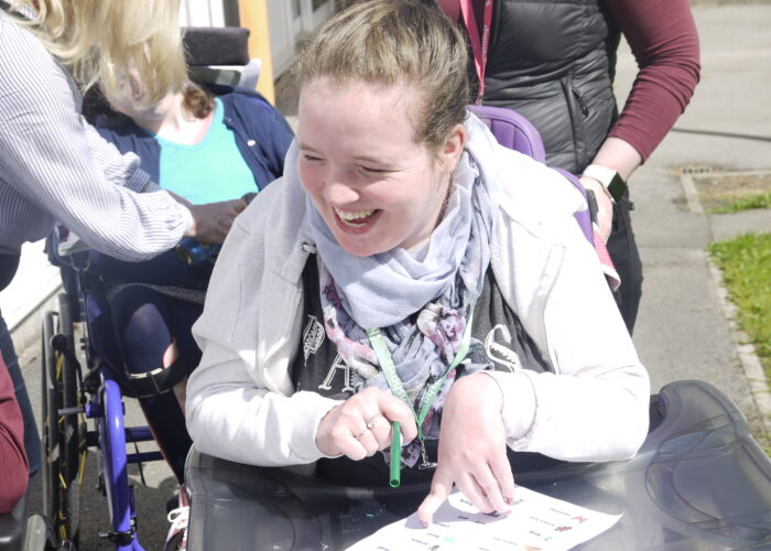 Student in a wheelchair smiling in the sun