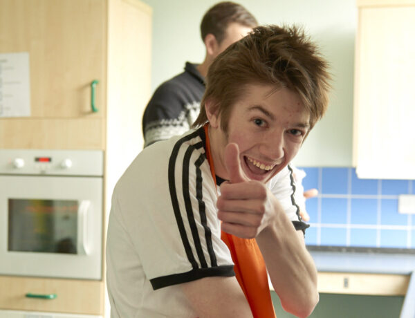 Student in the kitchen smiling and giving a thumbs up