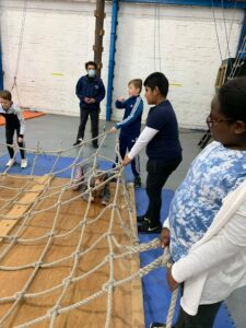 Group of children taking part in crawling through nets
