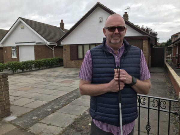 Man stood outside house with cane