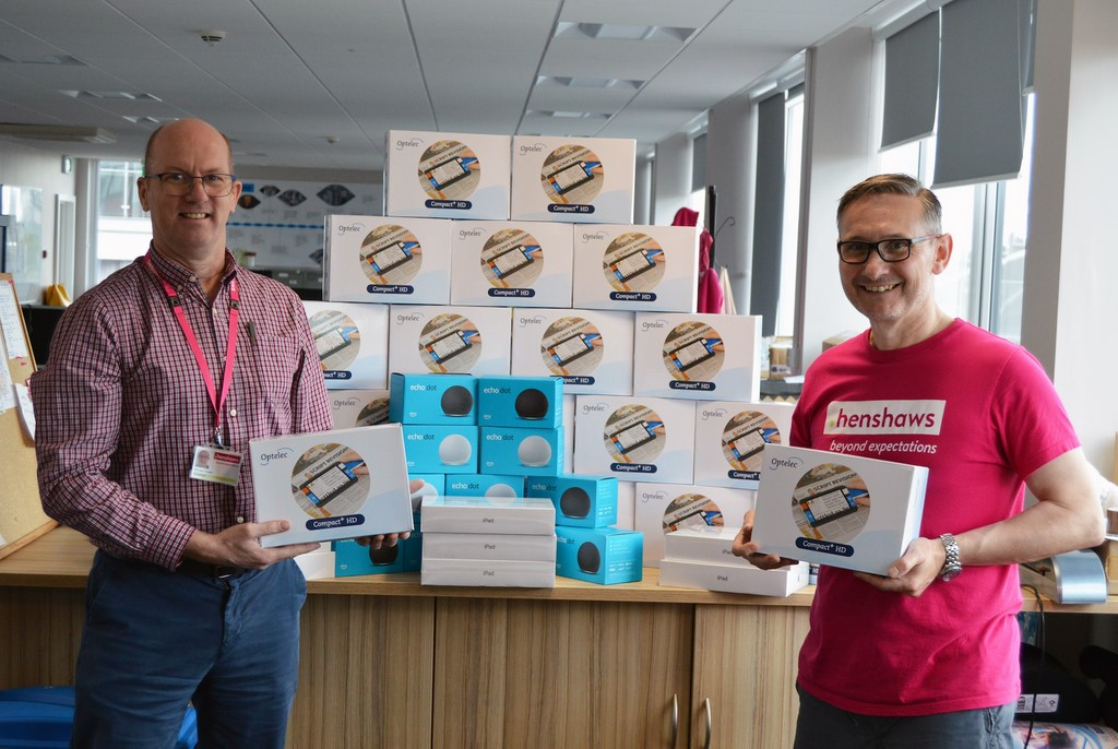Two men with boxes of Optelec magnifiers, boxes of Amazon Echos and iPads