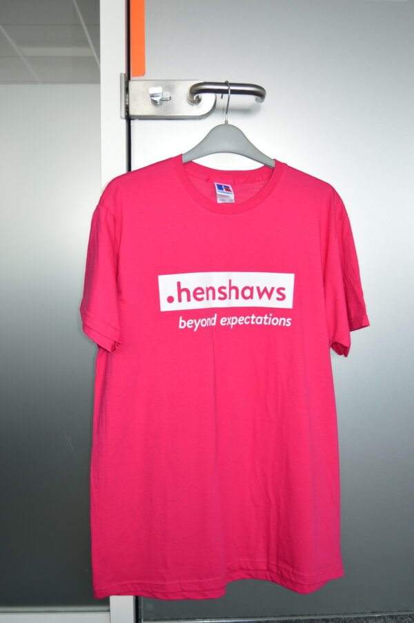 Pink T-shirt with Henshaws logo in write on the front