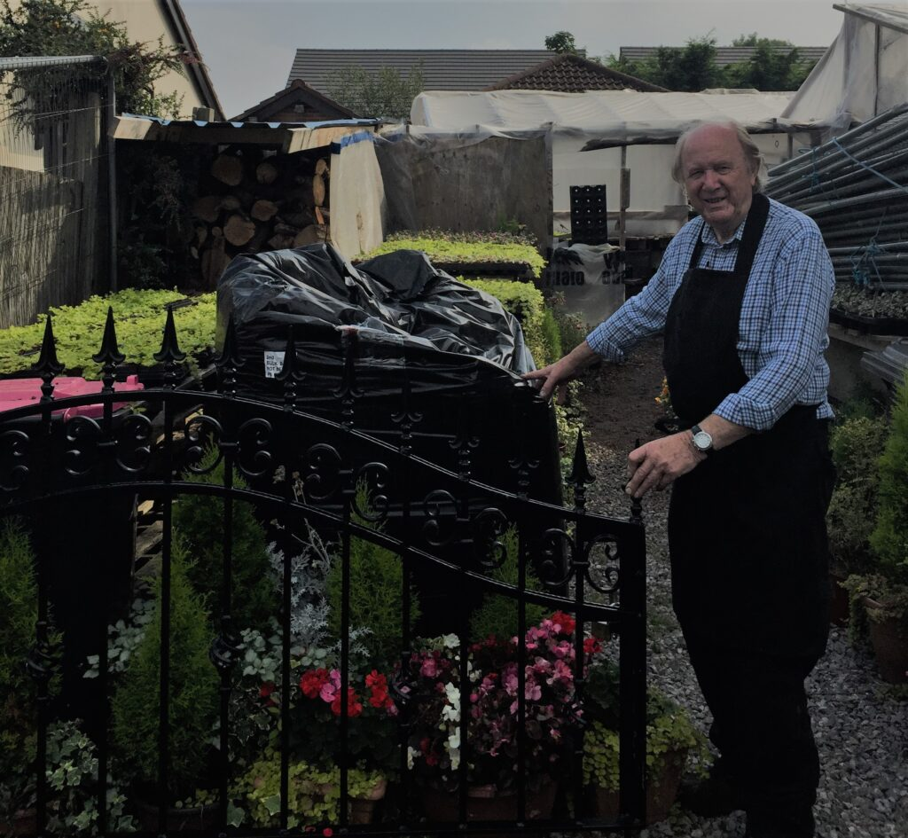 Geoff by his gate in the garden smiling