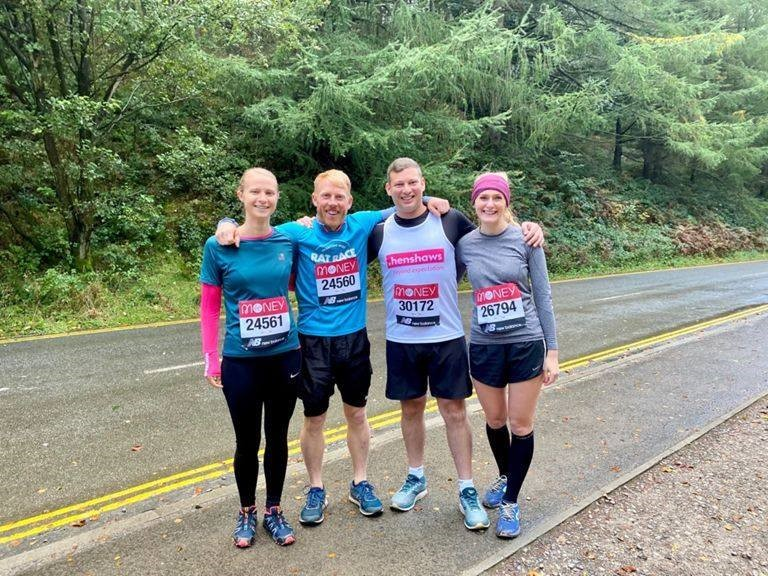 Four people smiling together during a marathon in Henshaws branded t-shirts